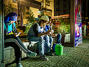 27 FEBRUARY 2019 - BANGKOK, THAILAND: Construction workers check their smart phones at the end of their shift on a high end condominium development in Bangkok. Bangkok, a city of about 14 million, is famous for its raucous nightlife. But Bangkok's real nightlife is seen in its markets and street stalls, many of which are open through the night.        PHOTO BY JACK KURTZ