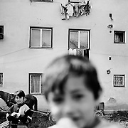 Children play in a housing estate in the heart of  the small Romanian town of  Copsa Mica, Transylvania, Romania. Copsa Mica was once described as the most polluted town in Europe. May 8, 2008. Photo Tim Clayton....Copsa Mica, a small industrial town deep in Transylvania, Romania, was described during the 1990s as the most polluted town in Europe with lead levels reaching were more than 1000 times the allowable International limits and life expectancy nine years shorter than the National average...The pollution was caused entirely by two factories, Carbosin produced black for dies and tires and closed in 1993 while Sometra, a nonferrous smelter is still operational today...The pollution was so bad sheep were black, covered in soot and health officials advised against eating livestock or vegetables and drinking the water or milk...The Communist rule of Nicolae Ceausescu is blamed for the widespread environmental degradation that left industrial parts of Romania in ecological disaster. Industry was situated in a way to concentrate pollution in small areas leaving the rest of the country relatively free of pollution.Copsa Mica in particular was left an environmental disaster...The pollution caused a direct affect on human health with widespread Lung disease, Impotency, the highest infant mortality rate in Europe, Lead poisoning andbehavioral problems...Fifteen years on since the closure of Carbosin in 1993, the factory skeleton remains as part of the towns bleak landscape, Unfinished communist style housing blocks still stand in the heart of the towns housing estate. The town's inhabitants arestill trying to recover from the long lasting effects of pollution...Recent survey's found the soil contained so much lead that it was 92 times above the permitted level; the vegetation had a lead content 22 times above the permitted level. While toxins have penetrated at least one meter (three feet) into the soil leaving the entire food chain in the area cont