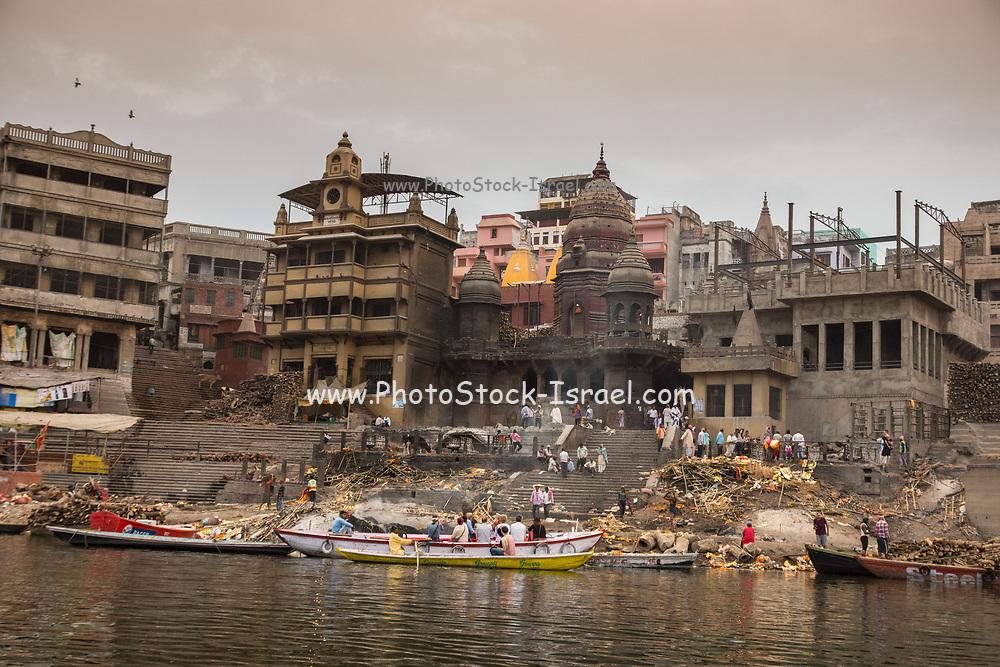 Pilgrims visiting the Holy city and colourful rowing boats on the Ganges river at Varanasi, Uttar Pradesh, India