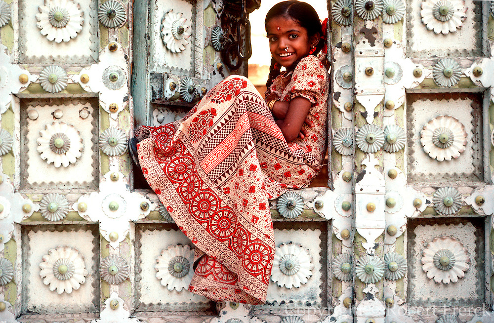 INDIA, PORTRAITS Portrait of Rajasthani girl seated in doorway of decorated Rajput fortress and palace in Jodhpur