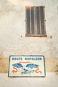 Sign of official starting point of the Route Napoleon under shuttered window on dilapidated building facade in the beach town of Golfe-Juan, France