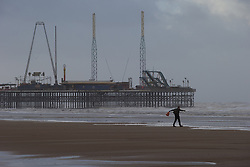 "© Licensed to London News Pictures . 10/12/2014 . Blackpool , UK . A lone man stands against the wind on Blackpool beach . An explosive cyclogenesis - a fast developing storm in which air pressure falls rapidly - known as a "" weather bomb "" - hits the North of England , bringing storms to the region . Photo credit : Joel Goodman/LNP"