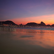 Praia de Copacabana at sunrise. Copacabana beach, one of the world's most famous urban beaches at sunrise with Sugar Loaf Mountain in the distance. The beach and hotel strip stretches for 1.5 miles (4km) from the Morro do Leme at the Northern end, to Arpoador at the South. Copacabana beach, Rio de Janeiro,  Brazil. 13th August 2010. Photo Tim Clayton.