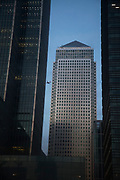 A plane flies behind Canary Wharf in London. In a strange scene reminiscient of some kind of 9/11 scene the financial district seems vulnerable to some kind of attack.