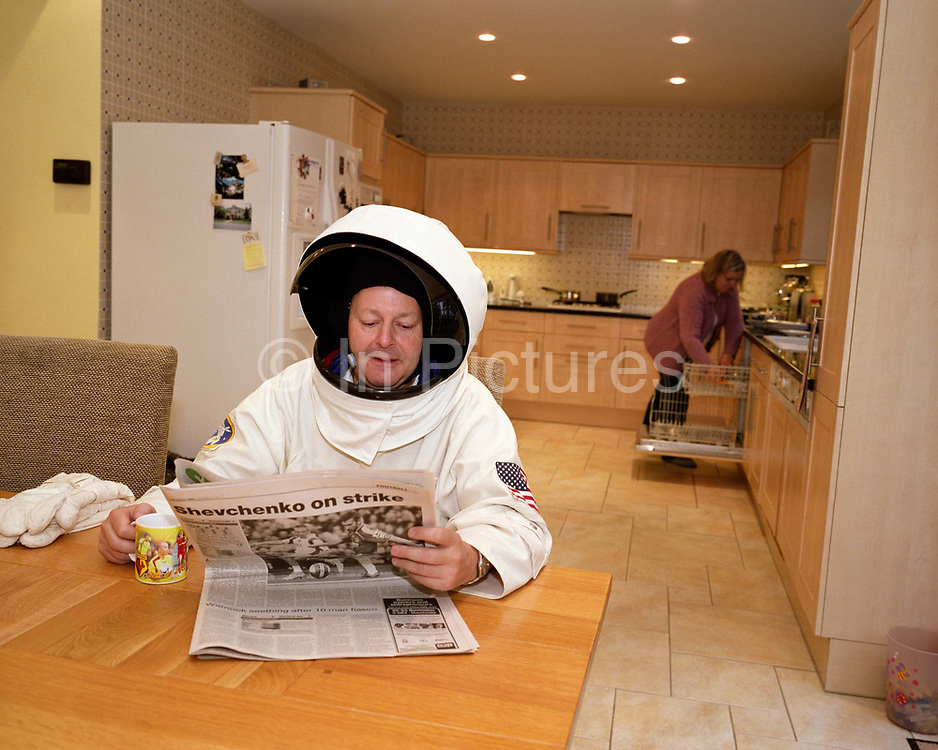 In the kitchen on a Sunday morning, space-suited frequent flyer astronaut Alan Watts reads the Sunday newspaper while his wife empties the dishwasher in his north London home, England. Alan, 51, runs an electrical company and qualified for a free space space flight after being contacted by Sir Richard Branson's Virgin Galactic space company, having accumulated 2 million air miles on the Virgin Atlantic flight network. Aboard the re-usable space vehicle will be 6 passengers, each of whom will have paid $200,000 for the 40 minute flight to 360,000 feet (109.73km, or 68.18 miles) and to experience just 6 minutes of weighlessness. Flights start around 2009/10 from a Mojave desert test facility but therafter, at the new Philippe Starck-designed SpacePort America, New Mexico, USA. a 27 square mile, $225 million headquarters facility near Las Cruces.