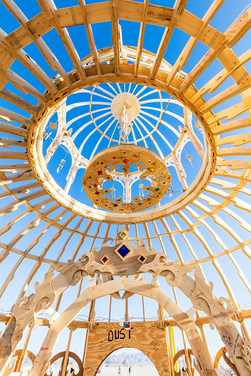 """Chapel of the Chimes<br /> by: Infinity Gathered<br /> from: Washington, D.C.<br /> year: 2019<br /> <br /> You happen upon this beautiful and curvaceous hand-cut building of wood and steel chimes. The love and care that went into each cut is visable. The Chapel of the Chimes awaits you.<br /> <br /> The love poured into the structure makes it a perfect place to have a ceremony with loved ones. There is an arch inside and platform to stand. Share your vows, commitments, and devotion here.<br /> <br /> You may also simply take shelter here from the hot sun and relax to the sound of the wind breezing through, giving the wind a different voice and experience. The chimes harmonize and sing you a song you've not yet heard.<br /> <br /> Come and learn of the playa-adjacent origins of the structure! It has quite a story to share. Come early, it burns before the end of the event!<br /> <br /> URL: http://www.infinitygathered.com<br /> <br /> https://burningman.org/event/brc/2019-art-installations/?yyyy=&artType=B#a2I0V000001AXizUAG<br /> <br /> (Thanks to reddit user <a href=""""https://www.reddit.com/r/BurningMan/comments/djq4fw/872_of_my_photos_from_burning_man_2019/f47tb3d/"""">sachin571</a> for the caption update)"""