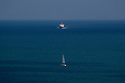 A single yacht sails in good time across the path of a P&O cross-channel ferry as it approaches Dover Harbour from France, on 16th September 1995, in Dover, Kent, England.