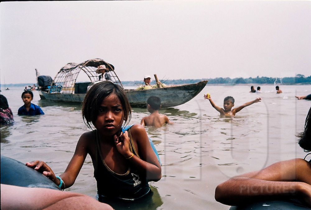 A young girl wades through the water collecting empty cans of beer and soft drinks to recycle, Mekong River, Cambodia, Southeast Asia