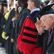 World War II veteran Bob Barger, 96, salutes during the national anthem before he graduated with an associate's degree during the graduation ceremony at the University of Toledo in Toledo on Saturday, May 5, 2018. He was joined at the ceremony by Navy Reserve officer Lt. Haraz Ghanbari, the school's director of military and veteran affairs. THE BLADE/KURT STEISS