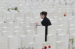 A woman touches a gravestone at the Tyne Cot Commonwealth War Graves Cemetery in Ypres, Belgium, ahead of commemorations to mark the centenary of Passchendaele.