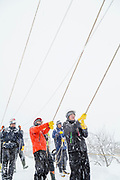 Group of people holding ropes in snow, Nozawaonsen, Japan