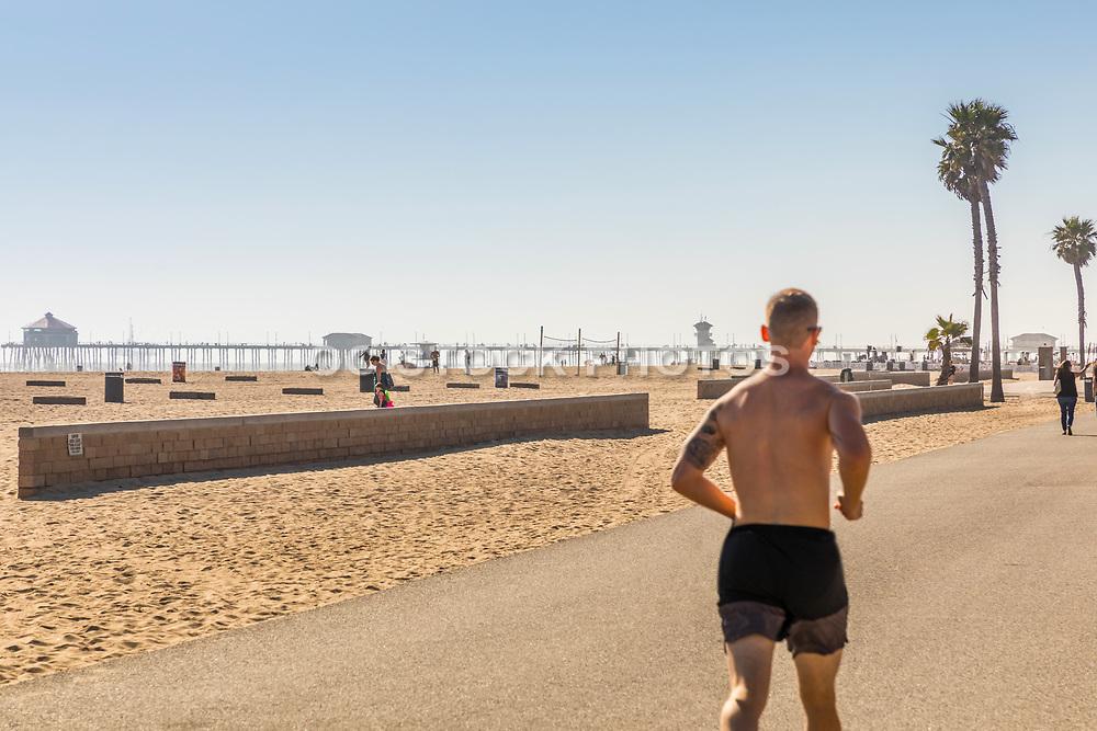 Man Running On Huntington Beach Boardwalk With Pier In Background