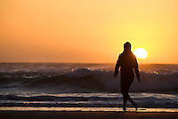 female walks along shore of Gold Bluffs beach as sun sets into Pacific ocean, California