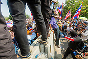 """09 DECEMBER 2013 - BANGKOK, THAILAND: Anti-government protestors scramble over barricades blocking the roads in front of Government House in Bangkok. Thai Prime Minister Yingluck Shinawatra announced she would dissolve the lower house of the Parliament and call new elections in the face of ongoing anti-government protests in Bangkok. Hundreds of thousands of people flocked to Government House, the office of the Prime Minister, Monday to celebrate the collapse of the government after Yingluck made her announcement. Former Deputy Prime Minister Suthep Thaugsuban, the organizer of the protests, said the protests would continue until the """"Thaksin influence is uprooted from Thailand."""" There were no reports of violence in the protests Monday.      PHOTO BY JACK KURTZ"""