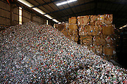 Mountains of aluminum cans piled high waiting recycling at a warehouse, operating big distribution for aluminium cans, and general metals, on the edge of Phnom Penh. Aluminium cans are sold with a street value of about 1$ the kilo, the small warehouse add 10% and all the cans are shipped. already sorted to the big distribution recycling warehouses outside Phnom Penh. Here the aluminium cans are squashed into bricks and stacked or placed in mountains for export to Thailand and Vietnam for truning back into the raw material.