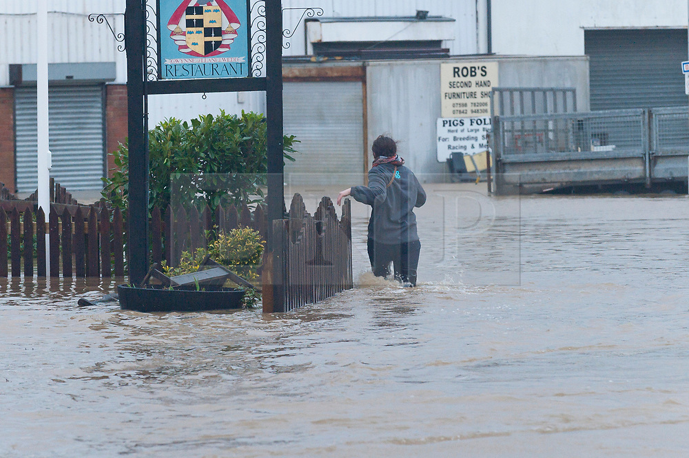 © Licensed to London News Pictures. 16/02/2020.  Builth Wells, Powys, Wales, UK. A woman wades through flood water to rescue her car. The river Wye bursts it's banks at Builth Wells in Powys, Wales, UK. after heavy rainfall yesterday and last night, causing the A483 road to be closed and traffic diverted. The river level broke the all-time high (5.05 m) at 08.30hrs  this morning at Builth Wells. According to Natural Resources Wales the highest recorded level at Builth Wells was 4.95m on 28/10/98 at 2:45 am (GMT) Photo credit: Graham M. Lawrence/LNP