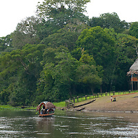A thatch-roofed tourist boat approaches The Amazon Refuge Wildlife Conservation Center, a tourist camp on Peru's Yanayacu River.