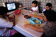 One of the local schoolchildren, Paco, with his grandmother and other family members, snacks on pan-fried chapulines, or grasshoppers, after school every day while watching TV in the family kitchen. Oaxaca, Mexico. (Man Eating Bugs page 112 Top)