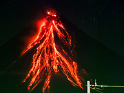 "22 JANUARY 2018 - LEGAZPI, ALBAY, PHILIPPINES: Lava flows from the cone of the Mayon volcano Monday night, as seen from Legazpi, about 12 kilometers from the volcano. There were a series of eruptions on the Mayon volcano near Legazpi Monday. The eruptions started Sunday night and continued through the day. At about midday the volcano sent a plume of ash and smoke towering over Camalig, the largest municipality near the volcano. The Philippine Institute of Volcanology and Seismology (PHIVOLCS) extended the six kilometer danger zone to eight kilometers and raised the alert level from three to four. This is the first time the alert level has been at four since 2009. A level four alert means a ""Hazardous Eruption is Imminent"" and there is ""intense unrest"" in the volcano. The Mayon volcano is the most active volcano in the Philippines. Sunday and Monday's eruptions caused ash falls in several communities but there were no known injuries.   PHOTO BY JACK KURTZ"