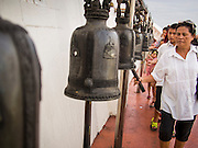 16 NOVEMBER 2013 - BANGKOK, THAILAND: People ring prayer bells at the Wat Saket temple fair. Wat Saket is on a man-made hill in the historic section of Bangkok. The temple has golden spire that is 260 feet high which was the highest point in Bangkok for more than 100 years. The temple construction began in the 1800s in the reign of King Rama III and was completed in the reign of King Rama IV. The annual temple fair is held on the 12th lunar month, for nine days around the November full moon. During the fair a red cloth (reminiscent of a monk's robe) is placed around the Golden Mount while the temple grounds hosts Thai traditional theatre, food stalls and traditional shows.    PHOTO BY JACK KURTZ