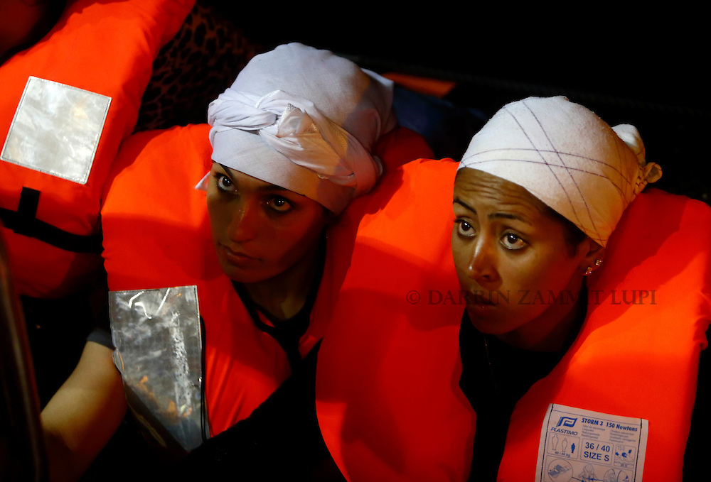 Migrants sit in a Migrant Offshore Aid Station (MOAS) RHIB (rigid hulled inflatable boat) alongside the MOAS ship MV Phoenix before being transferred to the Norwegian ship Siem Pilot off the coast of Libya August 6, 2015.  An estimated 700 migrants on an overloaded wooden boat were rescued 10.5 miles (16 kilometres) off the coast of Libya by the international non-governmental organisations Medecins san Frontiere (MSF) and MOAS without loss of life on Thursday afternoon, according to MSF and MOAS, a day after more than 200 migrants are feared to have drowned in the latest Mediterranean boat tragedy after rescuers saved over 370 people from a capsized boat thought to be carrying 600.<br /> REUTERS/Darrin Zammit Lupi <br /> MALTA OUT. NO COMMERCIAL OR EDITORIAL SALES IN MALTA