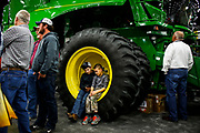 Craig Simpson, 13, middle-left, and John Davis, 10, middle-right, both from Elizabeth, Ind., rest on the wheel of a John Deere corn head during while their parents talk with others.