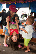 """17 MAY 2010 - BANGKOK, THAILAND: A woman plays with her children in Wat Pathumwanaram Monday. More than 800 people, mostly women and children, have gathered at Wat Pathumwanaram, near the Red Shirt protest area, hoping the Thai army will not attack them in the temple. The official start of the crackdown is expected to start about 15.00 Bangkok time Monday. The Thai government announced Monday that the Red Shirts unofficial military commander and supporter, Thai Army Maj. Gen. KHATTIYA """"Seh Daeng"""" SAWASDIPOL, died Monday from wounds he suffered when a sniper shot him in the head on May 12 while he was being interviewed by an American reporter. When the announcement was read to the Red Shirt protesters still camped out in Ratchaprasong intersection in Bangkok many started weeping.   PHOTO BY JACK KURTZ"""
