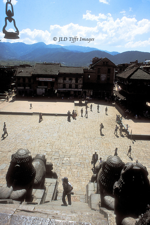 View across Durbar Square toward the countryside beyond from the upper platform of the Nyatapola Temple.  The square is empty except for a scattering of a dozen or so people walking about.
