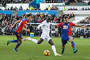 Modou Barrow of Swansea City has a shot, under pressure from James McArthur of Crystal Palace during the Premier League match between Swansea City and Crystal Palace at the Liberty Stadium, Swansea, Wales on 26 November 2016. Photo by Andrew Lewis.