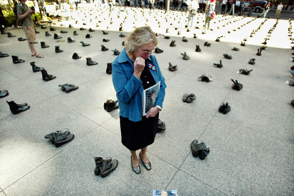 """Celeste Zappala of Philadelphia stands over a combat boot tagged with the name of her son Sherwood Baker holding his photograph in the middle of an exhibit of over 1000 pairs of combat boots bearing name tags of U.S. soldiers killed in Iraq.  The boots fill Federal Plaza in Chicago as part of an exhibit called """"Eyes Wide Open: The Human Cost of War in Iraq"""".   The exhibit was put on by the American Friends Service Committee.  For more information see www.eyes.afsc.org.  Baker, a national guardsman,  was 30 when he was killed in an explosion on April 26th of this year.  He was married and had a nine-year-old son.  Zappala says, """"This war was a mistake, a disaster.  It was a betrayal.""""  She continues, """"I don't think the administration has any idea what they've let loose or how to solve it."""""""