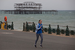 © Licensed to London News Pictures.  03/05/2021. Brighton, UK. A member of the public jogs along cost line of Brighton Beach in East Sussex, following The May Day, bank holiday as forecasts predict strong winds and rain for the coming week. Photo credit: Marcin Nowak/LNP