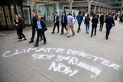 © Licensed to London News Pictures. 04/06/2018. London, UK. Pedestrians walk past graffiti on the pavement outside Labour Party headquarters protesting against the expansion of Heathrow Airport. Photo credit: Rob Pinney/LNP