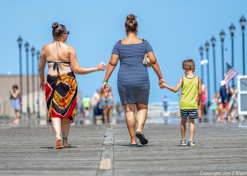A family heads for a day at the beach along the boardwalk in Asbury Park.