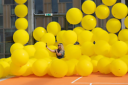 © Licensed to London News Pictures. 23/09/2021. London, UK. Visitors play in a rooftop basketball court with brightly coloured yellow balls in an installation titled Ball Court by CUSTHOM. The Design District in the Greenwich Peninsula is a permanent home for the creative industries. Featuring 16 buildings by eight pioneering architects, affordable spaces, comprehensive facilities and flexible leases. Photo credit: Ray Tang/LNP