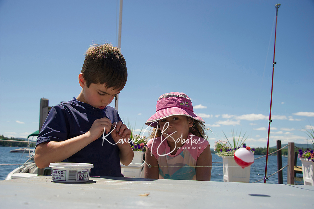 Sam Medue baits his hook with Sofia Sharood as they get ready to go fishing from the docks at The Windrifter Resort in Wolfeboro Bay.  (Karen Bobotas/Photographer)