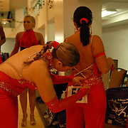 Same-sex ballroom dancers Hayley Perreira, left, puts a number on the outfit of her dance partner Sharon Vickers, both of Reading, England, before the women's latin competition at the 5 Boro Dance Challenge on May 5, 2007...In background are their teammates Jeannette Green, left, and Lorraine Vickers...The locally produced 5 Boro Dance Challenge, New York City's first major same-sex dance competition, was held at the Park Central Hotel in Manhattan from May 4-6, 2007. .
