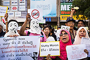 """09 JUNE 2013 - BANGKOK, THAILAND: A Thai Muslim women, and other members of the White Masks, protest against the government of Yingluck Shinawatra at Central World. The White Mask protesters wear the Guy Fawkes mask popularized by the movie """"V for Vendetta"""" and the protest groups Anonymous and Occupy. Several hundred members of the White Mask movement gathered on the plaza in front of Central World, a large shopping complex at the Ratchaprasong Intersection in Bangkok, to protest against the government of Thai Prime Minister Yingluck Shinawatra. They say that her government is corrupt and is a """"puppet"""" of ousted (and exiled) former PM Thaksin Shinawatra. Thaksin is Yingluck's brother. She was elected in 2011 when her brother endorsed her.       PHOTO BY JACK KURTZ"""