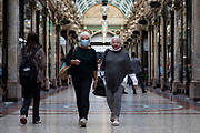 Two women, one wearing a face covering to protect from Covid-19, walk through a shopping arcade with bags on 4th September, 2021 in Leeds, United Kingdom. Despite a rise in footfall across the UKs high streets, new data has shown more than 8,700 chain stores have closed permanently, with the Covid-19 pandemic seeing consumer habits shifting in favour of shopping online or locally.