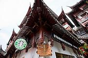 Starbucks coffee shop, American influence, alongside Chinese street signs in Yu Garden Bazaar Market, Shanghai, China