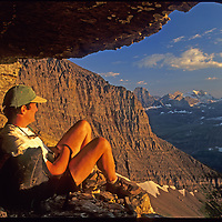 A mountaineer looks at mountains along the Continental Divide from a bivouac cave on Mount Gould, in Montana's Glacier National Park.