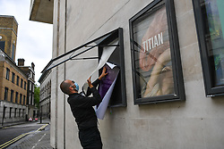 © Licensed to London News Pictures. 08/07/2020. Trafalgar Square, London, UK. Staff member Alexandro swaps out a poster as the National Gallery reopens its doors to the public after a closure of 111 days. Visitors are allowed into the gallery at controlled intervals having booked time slots online as the institution applies social distancing during the coronavirus outbreak. Photo credit: Guilhem Baker/LNP.
