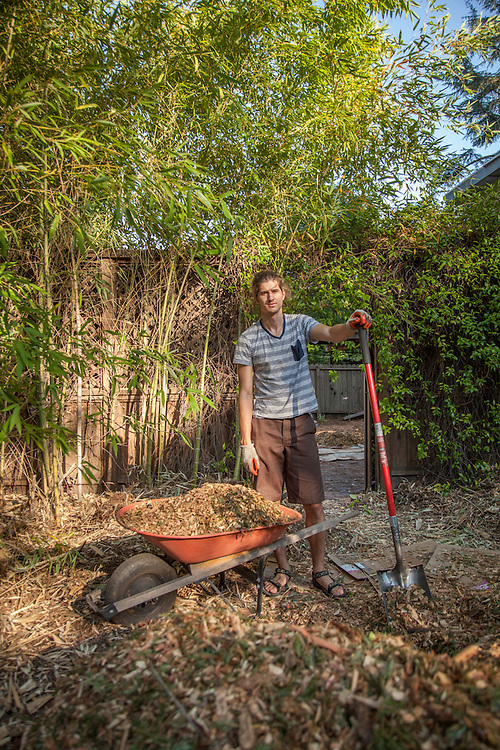 Recent UCLA graduate Taft Crowley helps his mother spread wood chips at her home in Calistoga