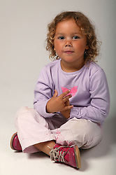 Portrait of young girl sitting cross legged on the floor,