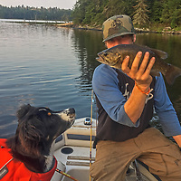 Ben Wiltsie displays a bass he caught while fishing with his dog Evie.
