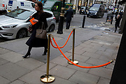A lady carrying an envelope walks past a matching new orange rope barrier outside a restaurant bar in Mayfair, on 5th January 2019, in London, England.