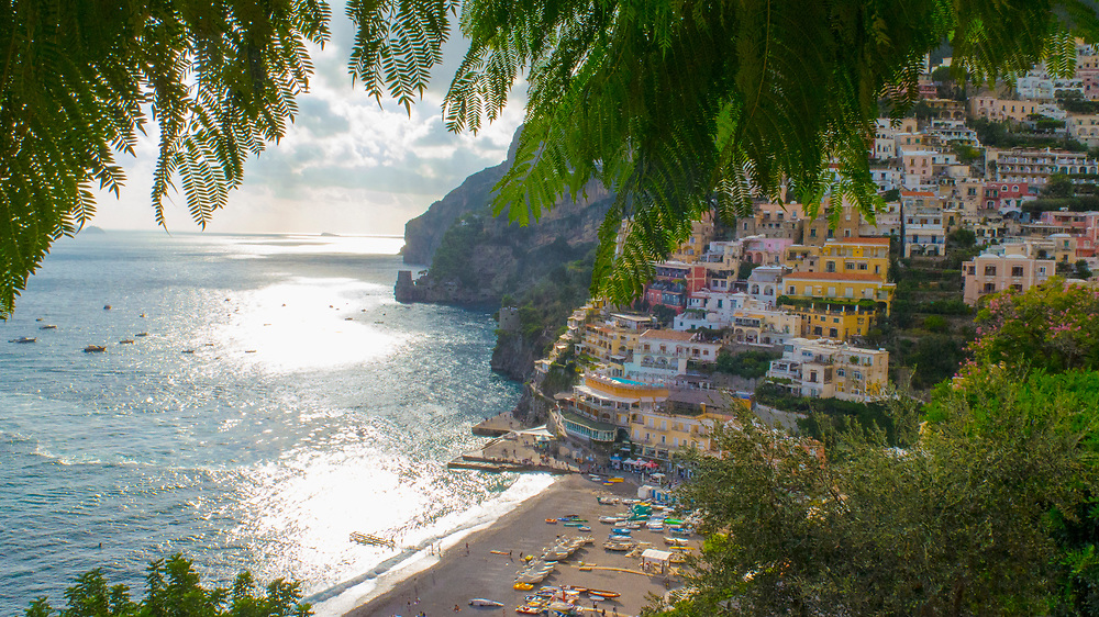 Colorful Buildings in Positano and Mediterranean Sea with palm trees in foreground
