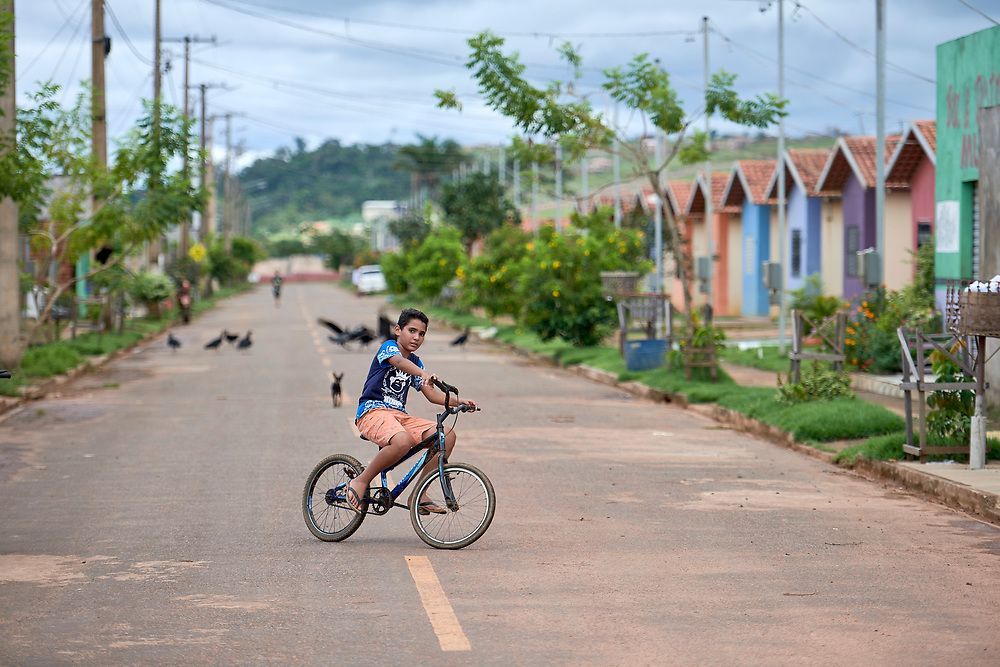 His family forced by the construction of the Belo Monte Dam to leave their village along the Xingu River, a boy today rides his bike through the crowded housing project built for displaced families outside Altamira, Brazil. Because the area where they were resettled is outside the city and has no phone service and little transportation, many people have moved away temporarily or permanently.