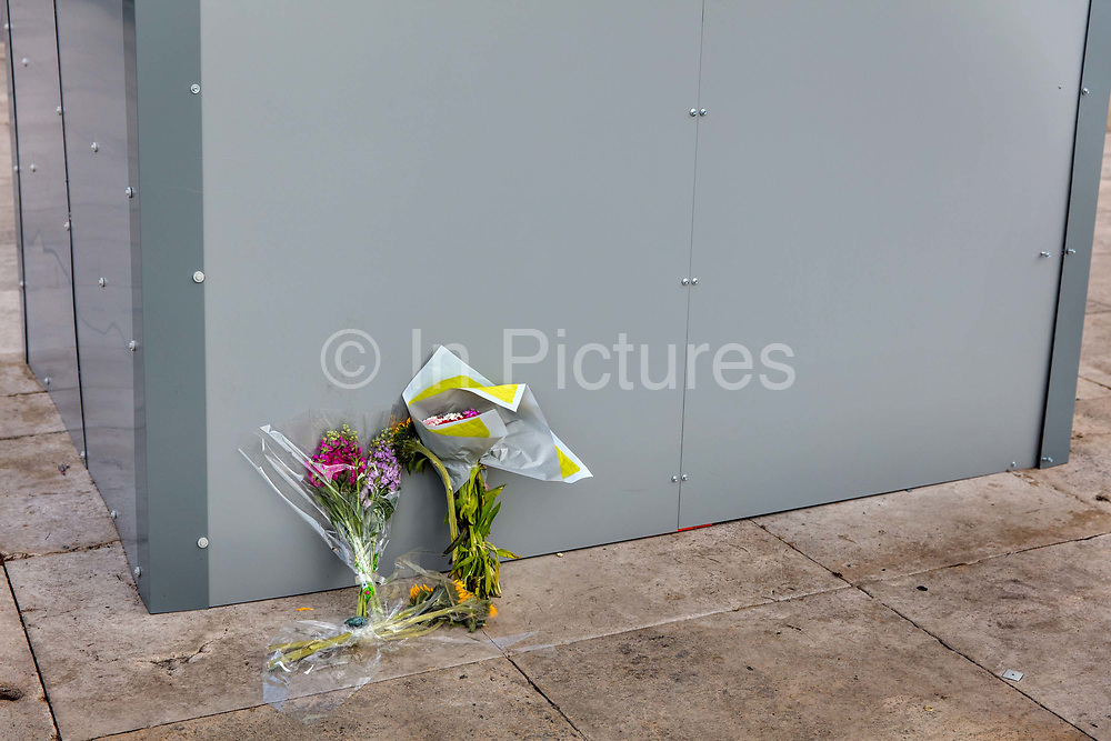 """Flowers left in front of the protective cover on a bronze sculpture by Ivor Roberts-Jones of the former British prime minister Winston Churchill on 15th June 2020 in Londons Parliament Square, United Kingdom. The statue was boarded up to protect it from attacks by Black Lives Matter protesters who sprayed graffiti on it over two successive days, including the words was a racist. Despite his achievements, there is evidence to suggest Mr Churchill was a white supremacist.<br /> He referred to British imperialism as being for the good of the """"primitive"""" and """"subject races"""". As a junior member of parliament, Mr Churchill supported Britain's plan for additional conquests, stressing that """"Aryan stock is bound to triumph""""."""