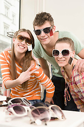 Friends trying sunglasses and having fun, smiling