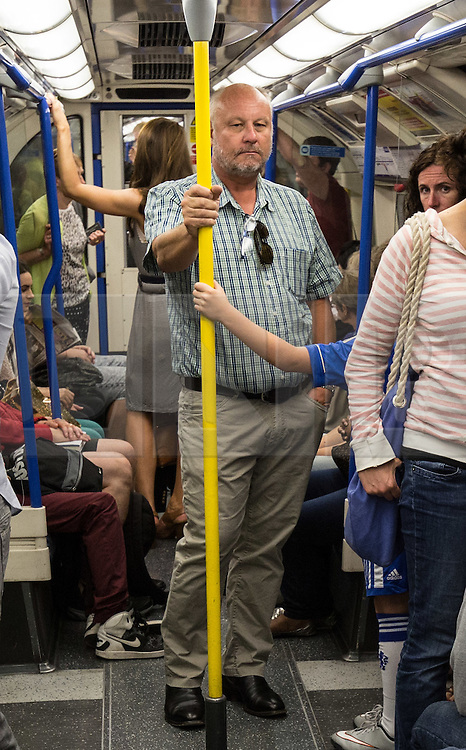 © Licensed to London News Pictures. 07/07/2015. London, UK. People observing a one minute silence on a westbound Piccadilly Line train at Kings Cross Station today, the same route which was taken by Germaine Lindsay, who killed 26 people in the 7th July 2005 bombings in London which killed 52 people in total. Photo credit : James Gourley/LNP